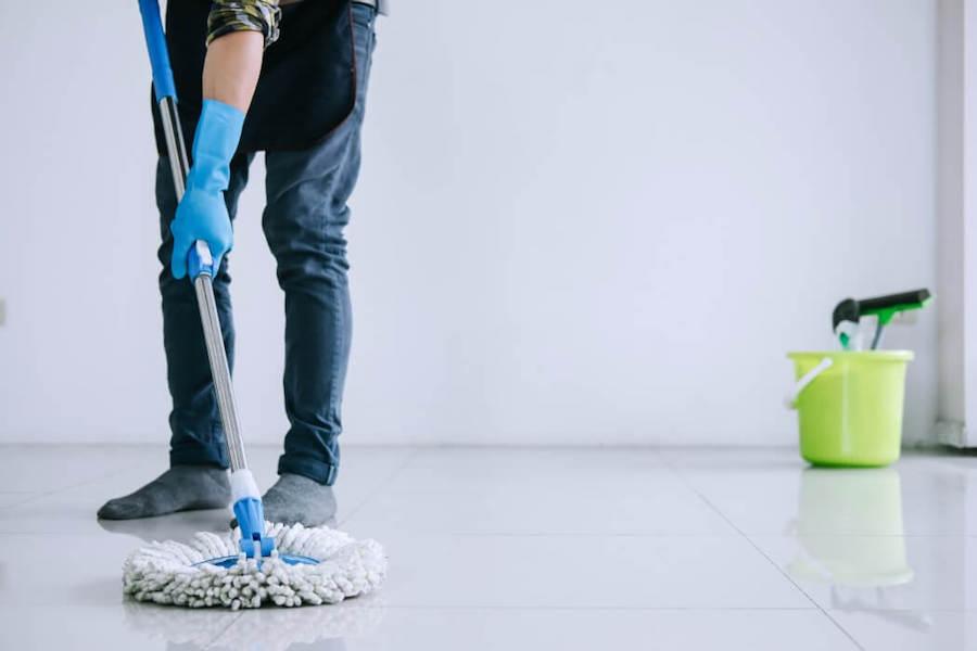 Man som moppar golvet i ett vitt rum